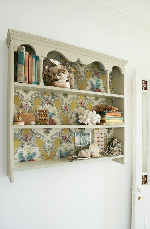 A book case decorated with wallpaper by deborah bowness.